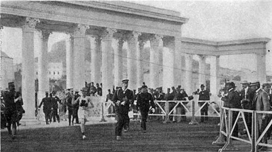 Jorge de Grecia, uniformado, corriendo al lado del vencedor del oro.