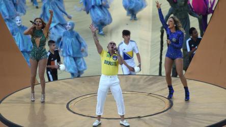 Pitbull canta al lado de una caricaturización de los uruguayos.