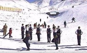 NIños bailan con dagas en una competencia de Cirit bajo la nieve, mientras transita gente que nada tiene que esquiar dentro de un campo de juego.